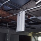 Light fixture without adequate independent support dangling along one edge from ceiling grid. Haiti Earthquake